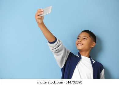 African American boy with cellphone on blue background