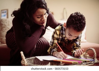 African American boy drawing at home with his mother.