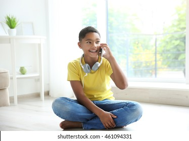 African American boy with headphones and cellphone at home