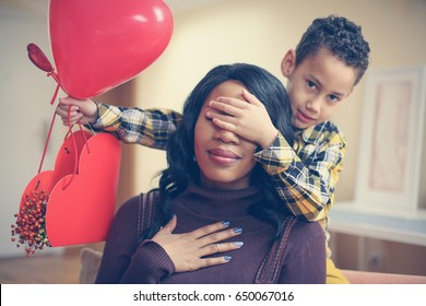African American boy holding his mother closed eyes. Looking at camera.
