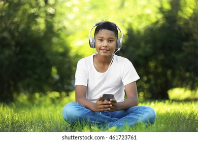 African American boy listening music in park