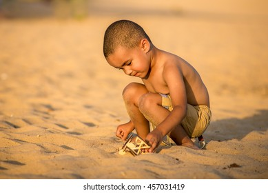 African American boy playing airplane on the beach