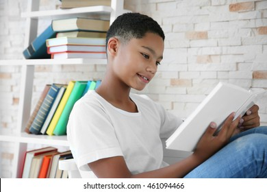 African American boy reading books in stylish library