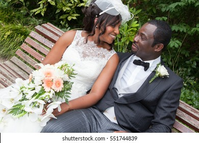 African american bride and groom kissing in the park in the wedding and marriage day