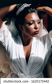 African American bride in lingerie and bathrobe in the morning preparing for the wedding in a hotel room