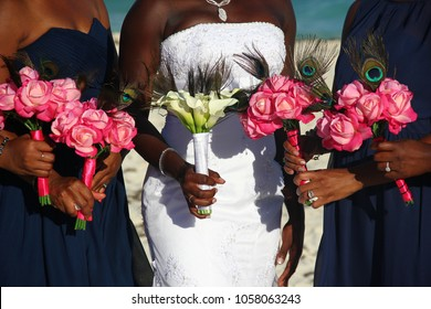 African American bride on white dress together with bridesmaids holding colorful flower bouquets on wedding day outdoors. Detail on glamorous ceremony event closeup. Happiness concept