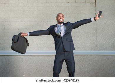 African American business man is happy standing on a gray background urban wall