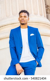 African American Business Man with little goatee, working in New York, wearing blue suit, unbuttoned, white T shirt, standing by columns on street, thinking, looking forward. Color filtered effect