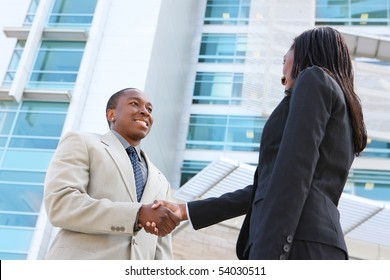 An african american business man and woman team handshake at office building