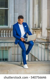 African American Business Man working in New York, wearing blue suit, white sneakers, sitting on railing in office building, looking down, working on laptop computer, smiling. Color filtered effect