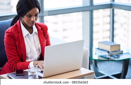 African American business woman busy looking at her computer screen while working on her notebook in the lounge of her business while seated a comfortable couch.