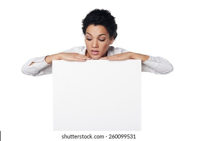 African american business woman standing behind blank white banner,peering over the edge, over white background
