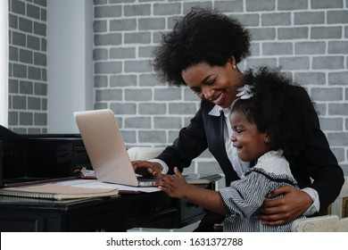 african american business woman taking care of her little daughter while working at home