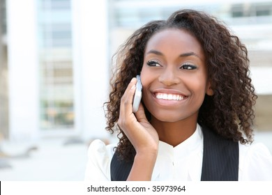 African american business woman talking on a  cell phone in front of an office building