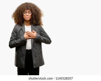 African american business woman wearing glasses smiling with hands on chest with closed eyes and grateful gesture on face. Health concept.