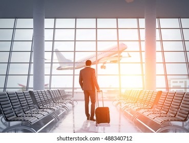 African American businessman in airport waiting area looking at large jet coming off the ground through panoramic window. Concept of business trips. Toned image