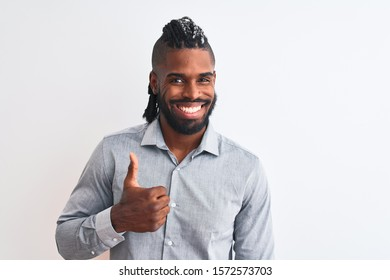 African american businessman with braids standing over isolated white background doing happy thumbs up gesture with hand. Approving expression looking at the camera with showing success.