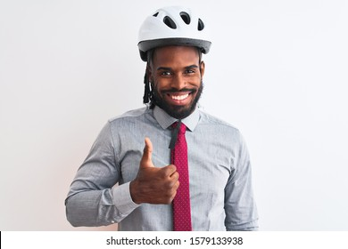 African american businessman with braids wearing bike helmet over isolated white background doing happy thumbs up gesture with hand. Approving expression looking at the camera with showing success.