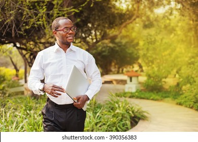 african american businessman carrying laptop walking in a park