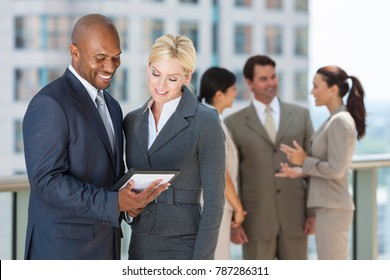 African American businessman and caucasian businesswoman using tablet computer or iPad with interracial group of business men & women team.