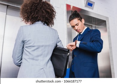 African american businessman checking his watch and waiting for elevator