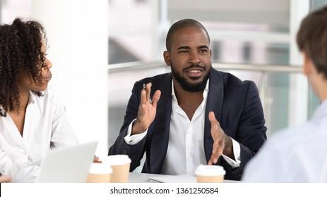 African american businessman coach leader negotiator speaking at diverse team meeting seminar, black male mentor talking teaching office employees group at international negotiation training workshop