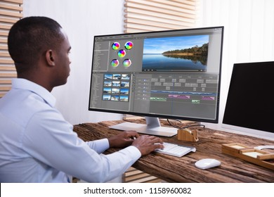 An African American Businessman Editing The Video On Computer Over The Wooden Desk