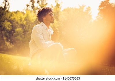 African American businessman having meditation in park.