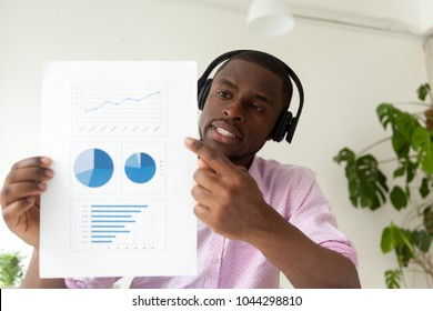 African american businessman in headphones talking by business corporate video call showing infographic statistics, black man holding document with graphs reporting distantly online, web camera view