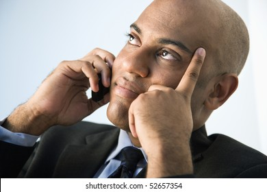 African American businessman holding cellphone to ear.