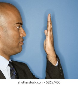 African American businessman holding hand in front of face.