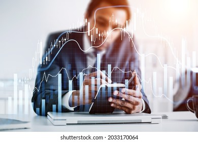 African American businessman is holding notebook and taking notes. Office workplace with laptop in the background. Forex candlestick and financial graph in the foreground. Concept of trading