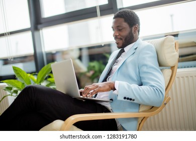 African american businessman in a light blue formal jacket and black pants making online shopping on laptop, sitting in comfortable arm-chair at office.