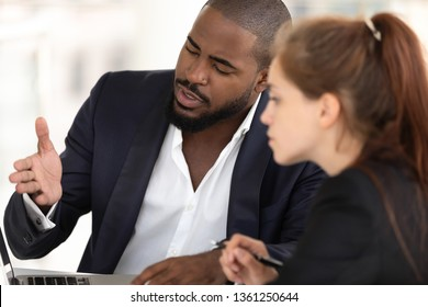 African american businessman mentor teaching caucasian intern with computer, serious black manager consulting talking to client selling services showing benefits on laptop at business meeting