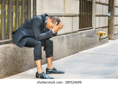 African American businessman in New York. Dressing in black suit, tie, leather shoes, wearing wristwatch, young black guy sitting on window on street, bending back, hands covering head, tired, sad.