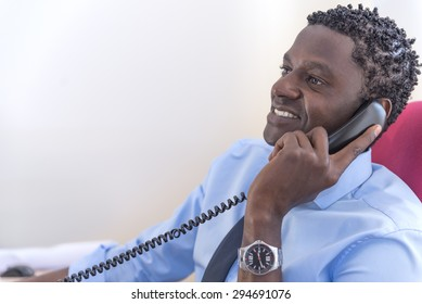 African American businessman on the phone sitting at the computer in his office