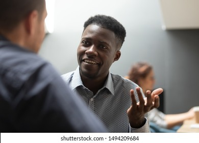 African american businessman professional manager talking to male caucasian colleague client discussing work project having friendly business conversation consulting customer teach intern in office