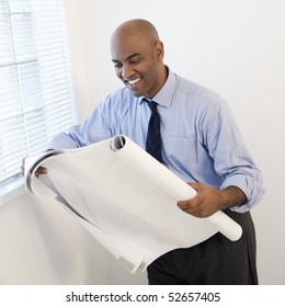 African American businessman reading architectural plans and smiling.