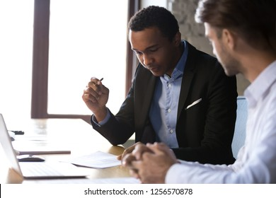African american businessman reading documents at meeting, black client or customer considering contract terms before signing checking legal paper law conditions preparing to make financial deal