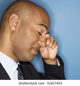 African American businessman rubbing his eyes.