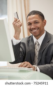 African American businessman sitting at the computer in his office holding up his credit card