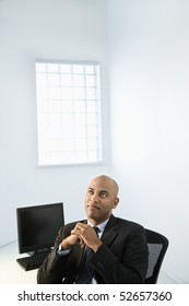 African American businessman sitting at office desk looking off in the distance.