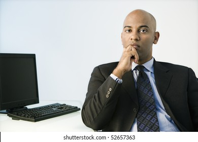 African American businessman sitting at office desk.