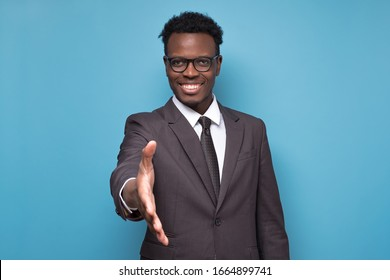 African american businessman in suit and glasses reaching out to shake hands making an agreement with his business partner. Studio shot on blue wall.