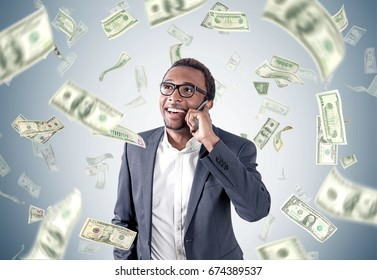 African American businessman in a suit is talking on a smartphone while standing near a gray wall with dollar bills falling around him.