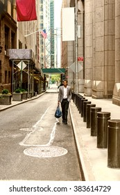 African American Businessman traveling, working in New York. Young black man walking on narrow old street with high buildings, carrying blue bag, wearing blazer, shirts. Color filtered effect.