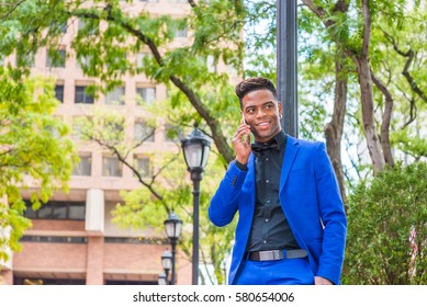 African American businessman travels, works in New York. Wearing blue suit, black shirt, bow tie, black man stands against light pole on street, listens, talks on cell phone.