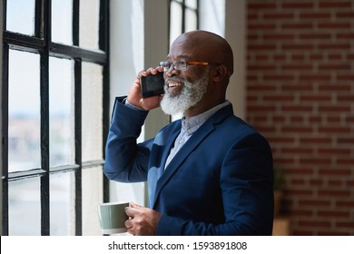 African american businessman using smartphone talking having phone call conversation in office looking out window