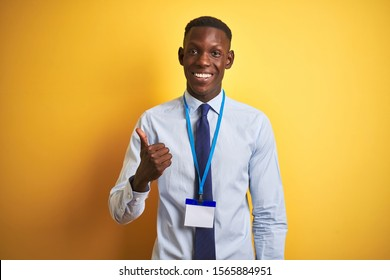 African american businessman wearing identification card over isolated yellow background doing happy thumbs up gesture with hand. Approving expression looking at the camera with showing success.