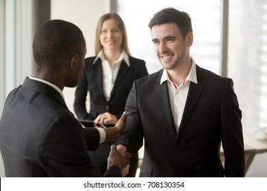 African american businessman welcoming and shaking hand with caucasian male and female business partners. Boss congratulating new employee with promotion, thanking for good job, sales results